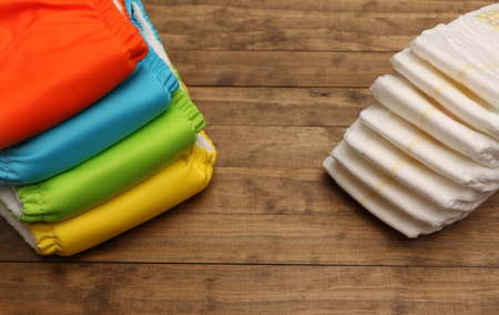 fabric cotton: Stacks of cloth and disposable diapers on a wooded background