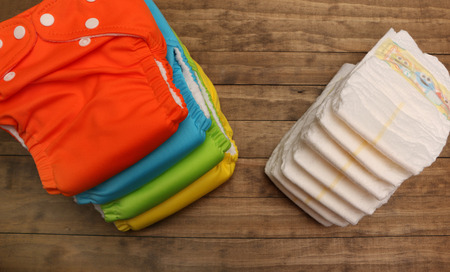 Stacks of cloth and disposable diapers on a wooded background