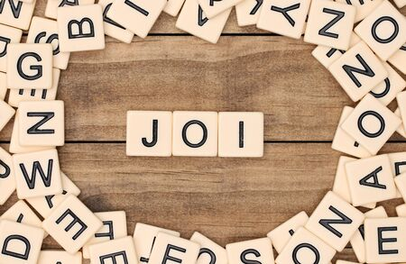 spelled: Joi - Joy in French spelled out in tan tile letters