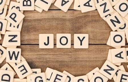spelled: Joy spelled out in tan tile letters Stock Photo