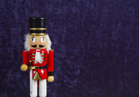 Wooden nutcracker in front of a blue velvet background