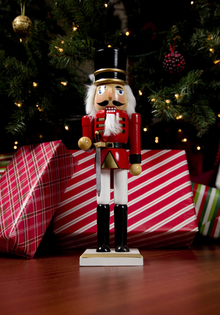 Nutcracker in front of a decorated tree with gifts