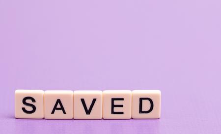 Saved Spelled Out in Tiles Imagens
