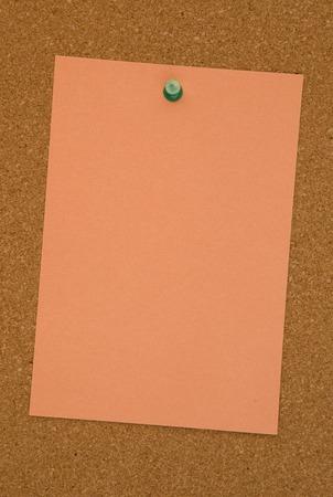 Blank Orange Paper on a Cork Board Stock Photo