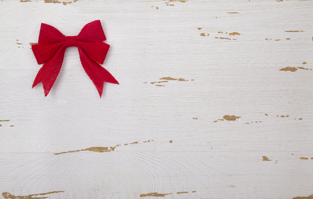 red christmas bows on a white wood table stock photo 93821061 - Red Christmas Bows