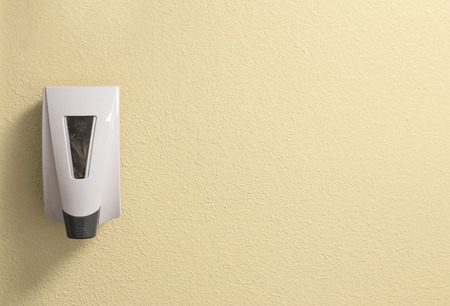 Generic Hand Sanitizer Dispenser on a Textured Cream Wall with Space to Add Writing or Text  Stok Fotoğraf