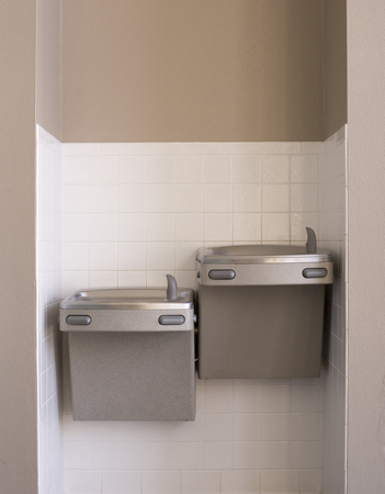Two indoor silver water fountains