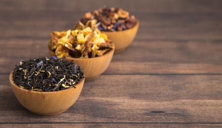 Loose Leaf Tea in a Wooden Bowl on a Wooden Table