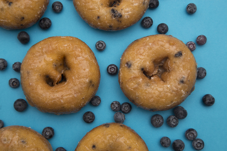 Blueberry Donuts with Scattered Blueberries on a Blue Background 스톡 콘텐츠