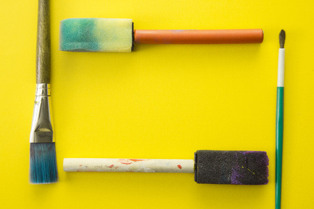 Childrens Paint Brushes on a Yellow Background Stock Photo