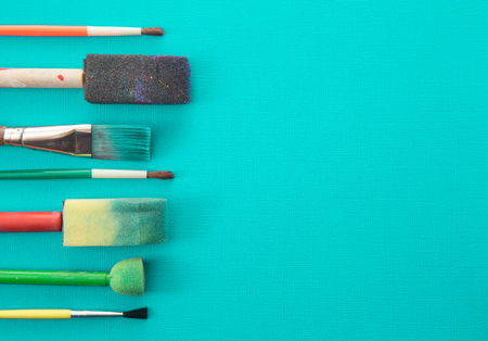 Childrens Paint Brushes on a Teal Background