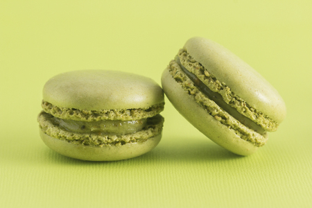 Green French Macarons on a Green Background 스톡 콘텐츠