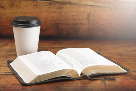 Bible and a Cup of Coffee in a Disposable Paper Cup on a Wooden Table
