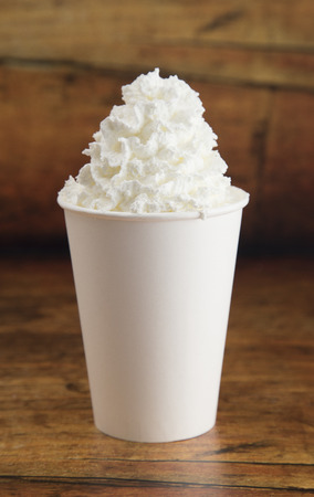 Drink with Whipped Cream on Top in a Disposable Cup on a Wooden Table