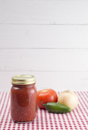 Salsa on a Red Gingham Table Cloth in a Home Canning Jar
