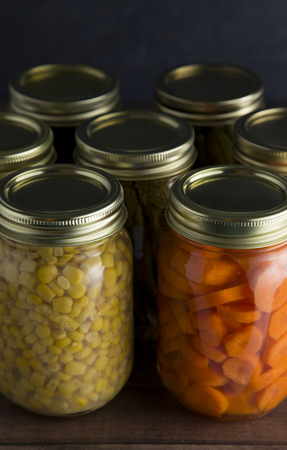 Various Types of Canned Vegetables on a Wooden Table in a Dark Environment