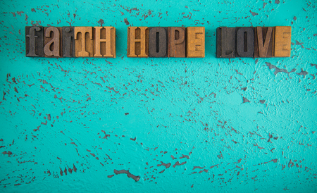 Faith Hope and Love Spelled in Wooden Type Set Block Letters on a Turquoise Background