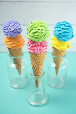 Rainbow Ice Cream Scoops in Waffle Cones on a Teal Table 스톡 콘텐츠
