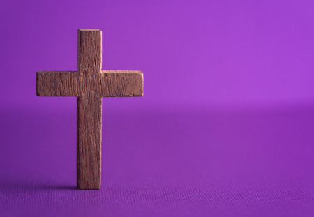 A Simple Wooden Cross on a Purple Background