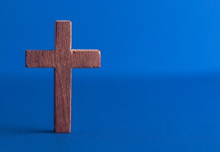A Simple Wooden Cross on a Blue Background