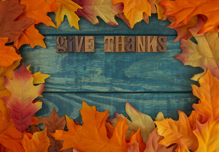 Give Thanks Background with Fall Leaves on Blue Wood