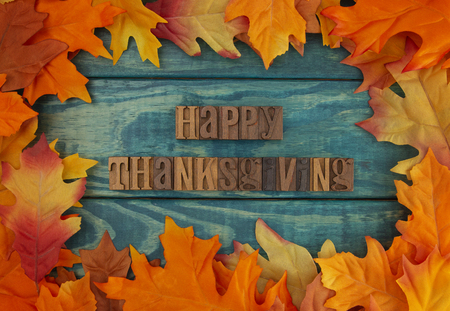 Happy Thanksgiving Background with Fall Leaves on Blue Wood