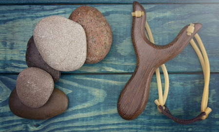 Slingshot and Five Smooth Stones on a Blue Table