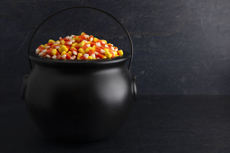 Black Cauldron For Witches FIlled with Candy Corn Archivio Fotografico