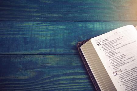 Święta Biblia na niebieskim drewnianym stole do nauki