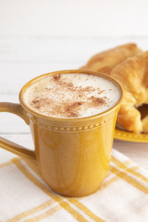 Cinnamon Topped Latte with Foamy Milk and Croissants in the Background