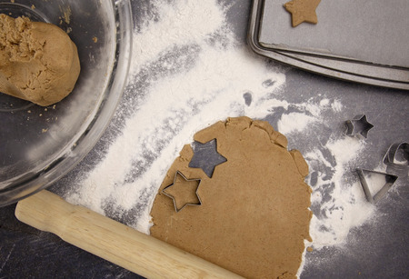 Gingerbread Cookies Being Rolled Out and Cut into Christmas Stars