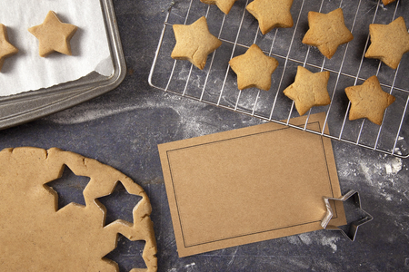 A Batch of Gingerbread Stars Being Made on a Dark Surface with a Blank Recipe Card 免版税图像