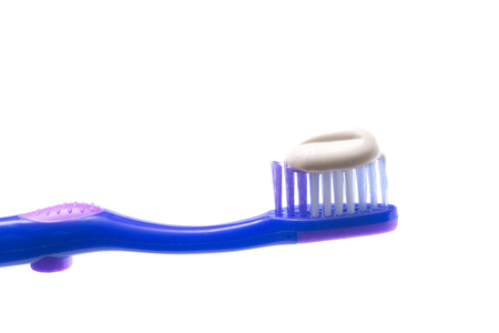 A Simple Toothbrush on a White Background with Toothpaste Applied to the Bristles
