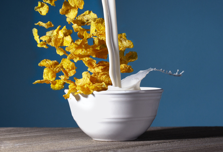 A Bowl of Healthy Corn Flakes with Splashing Milk for Breakfast