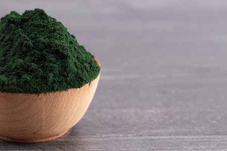 A Bowl of Spirulina Powder on a Wooden Table Imagens