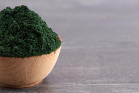 Un bol de poudre de spiruline sur une table en bois