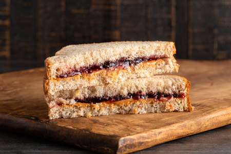 A Peanut Butter and Grape Jelly Sandwich on a Wooden Cutting Board Banque d'images