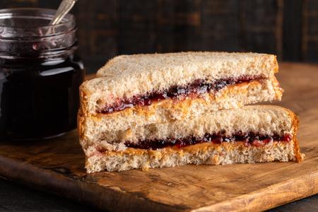 Un panino con burro di arachidi e gelatina d'uva su un tagliere di legno