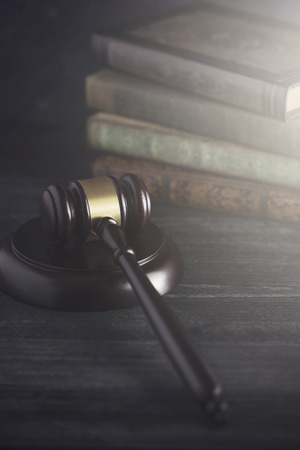 Wooden Judges Gavel on a Desk with Books in the Background