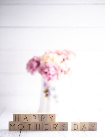 Mothers Day Background with Writing on Block Letters with Pink Flowers in a Vase