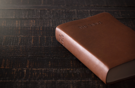 A Bible on a Wooden Table in a Dark Environment