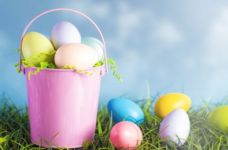 A Pink Easter Basket Filled with Diecorated Eggs on a Clear Blue Sky Spring Day Stock Photo