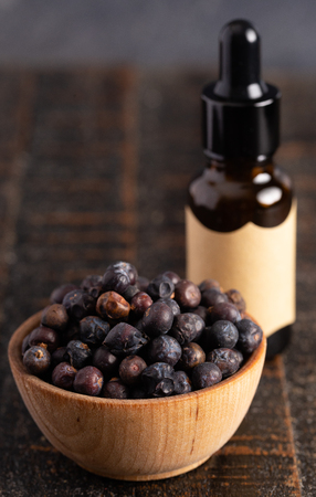 Juniper Berry Essential Oil on a Wooden Table