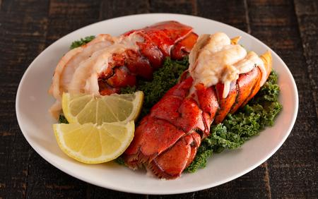 Deux queues de homard grillées sur un lit de chou frisé avec des tranches de citron