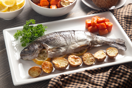 A Whole Baked Rainbow Trout on a Table Set for Dinner Banco de Imagens