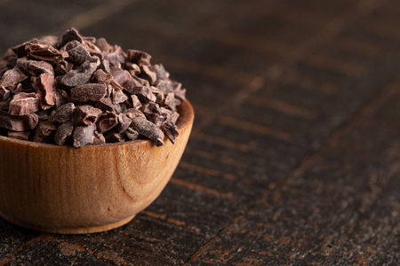A Bowl of Raw Chocolate Nibs on a Rustic Wooden Table Foto de archivo - 122562791