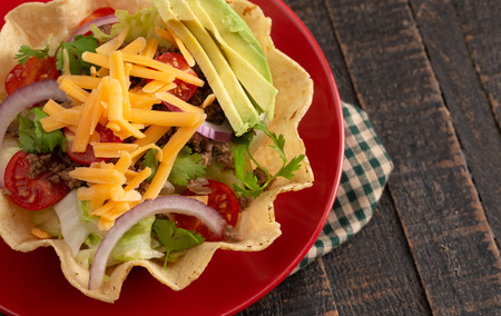 Taco Salad in a Crunch Corn Tortilla Bowl Isolated on a Wooden Table Фото со стока