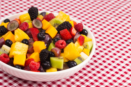 A Bowl of Fresh Rainbow Fruit Salad on a Red Plaid Tablecloth