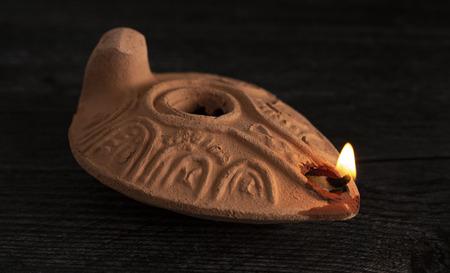 Lampada a olio fatta a mano accesa dal Medio Oriente su un tavolo scuro