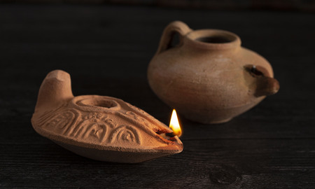 One Lit and One Unlit Handmade Oil Lamps from the Middle East on a Dark Table